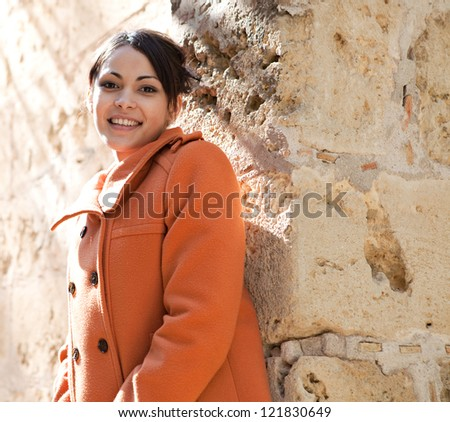 Young retro style woman wearing an orange coat and leaning on a sight's old stone walls while on vacation during a sunny day. - stock photo
