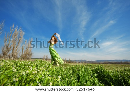 Young retro-styled girl posing in field - stock photo