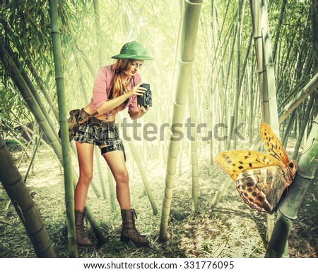 Young retro styled woman traveler in tropics holding vintage camera  photographed Big tropical butterfly - stock photo