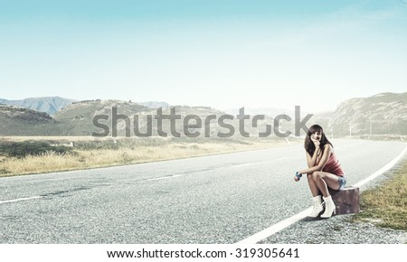 Young retro woman waiting on road with her vintage baggage