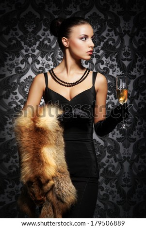 Young, rich and beautiful woman with the glass of champagne over the vintage background - stock photo