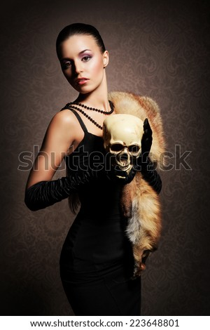 Young, rich and beautiful woman with the scull over the vintage background - stock photo