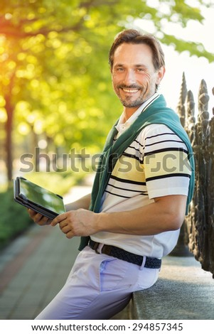 Young rich man posing with tablet PC in his hands. Handsome man smiling and looking very happy isolated in the green park.