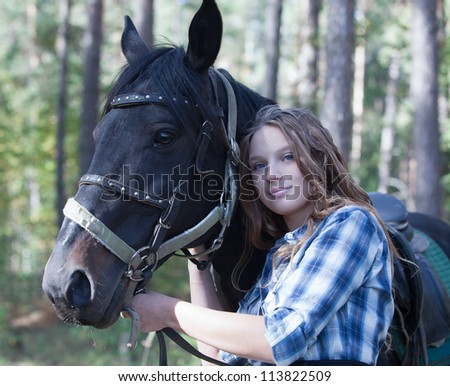Young rider hugging her horse in forest - stock photo
