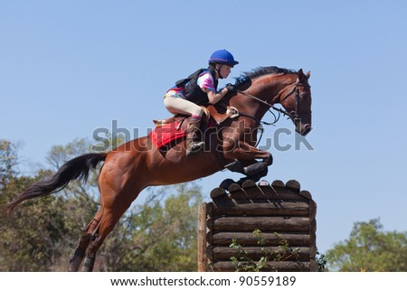 Young rider jumps a table on a cross country course - stock photo