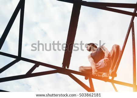 Young risky guy balancing and sitting on high metal construction