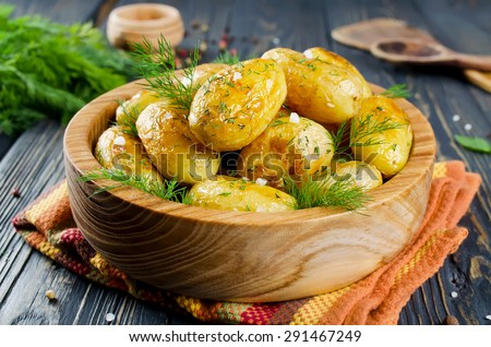 Young roasted potatoes with dill in a wooden bowl - stock photo