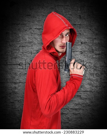 young robber with gun on a gray background - stock photo