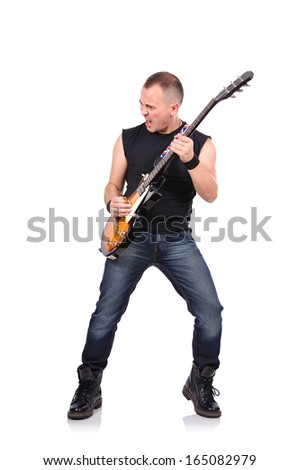 young rock musician is playing electrical guitar