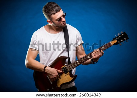young rock musician standing at guitar