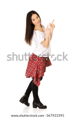 Young rock woman pointing up. - stock photo