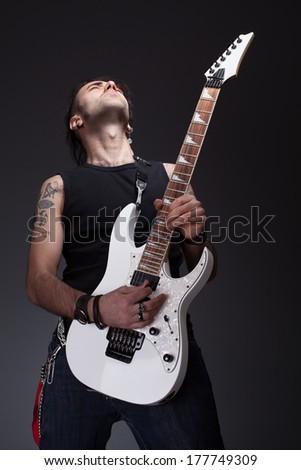 young rocker guy playing a white guitar - stock photo