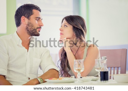 Young romantic brunette couple talking  at restaurant - stock photo
