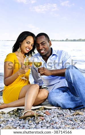 Young romantic couple celebrating with wine at the beach - stock photo
