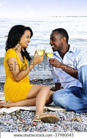 Young romantic couple celebrating with wine at the beach looking at each other - stock photo