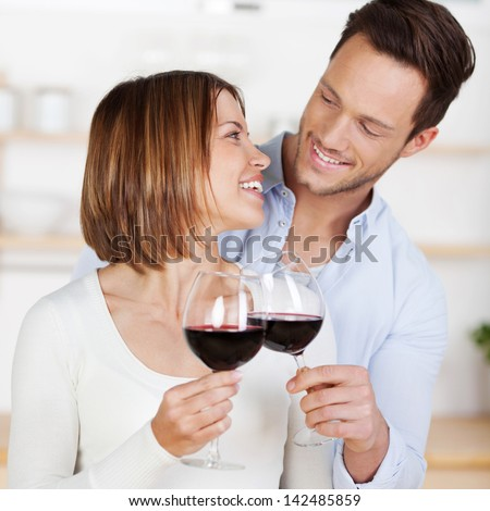 Young romantic couple cheers with red wine in a close up shot - stock photo
