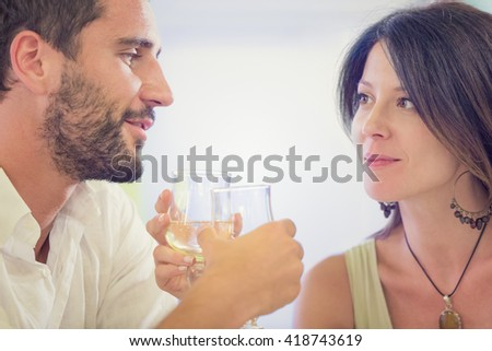 Young romantic couple drink to each other at restaurant