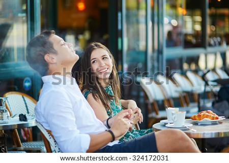 Young romantic couple drinking coffee, eating traditional French croissants and smoking in a cozy outdoor cafe in Paris, France - stock photo
