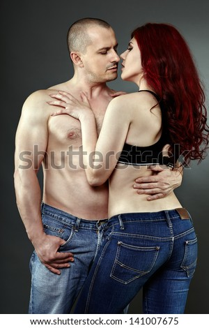 Young romantic couple embracing, foreplay, studio shot - stock photo