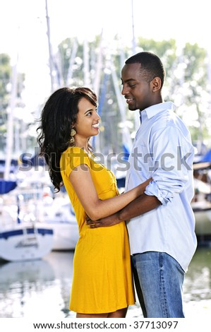 Young romantic couple facing each other hugging and standing at harbor - stock photo