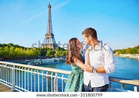 Young romantic couple having a date near the Eiffel tower on a bridge over the Seine in Paris, France - stock photo