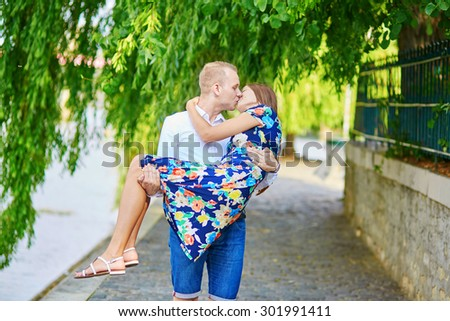Young romantic couple having a date on the Seine embankment in Paris, France. Man is holding his girlfriend in his arms - stock photo