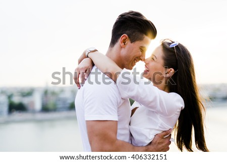 Young romantic couple hugging and about to kiss in beautiful sunset - stock photo