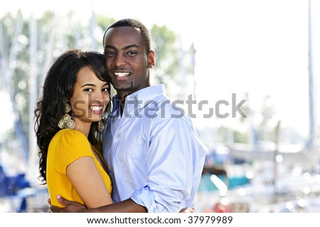 Young romantic couple hugging and standing at harbor - stock photo