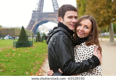 Young romantic couple hugging near the Eiffel Tower in Paris