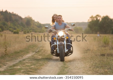 Young romantic couple in a field on a motorcycle - stock photo