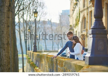 Young romantic couple in Paris, walking together on the Seine embankment on a sunny spring or summer day - stock photo