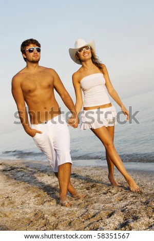Young romantic couple in white clothing walking on the seashore