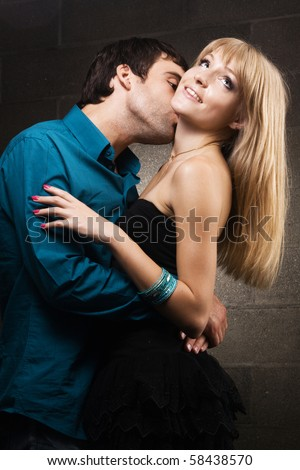 Young romantic couple kissing in house interior - stock photo