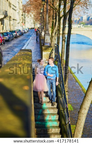 Young romantic couple on the Seine embankment in Paris, France