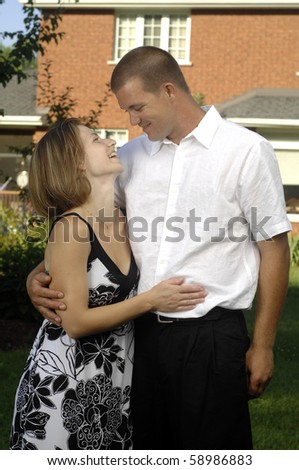 Young romantic couple plays in the backyard of their new home. - stock photo