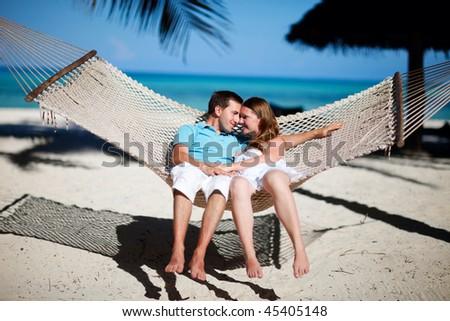Young romantic couple relaxing in hammock on tropical beach of Zanzibar island - stock photo