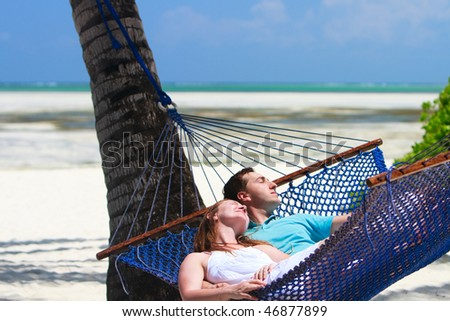 Young romantic couple relaxing in hammock on tropical beach of Zanzibar island - stock photo