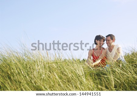 Young romantic couple sitting in tall grass at beach - stock photo