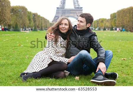 Young romantic couple sitting near the Eiffel tower - stock photo