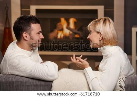 Young romantic couple sitting on sofa in front of fireplace at home, looking at each other, talking. - stock photo