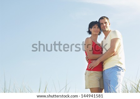 Young romantic couple standing in tall grass against clear blue sky - stock photo