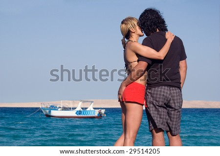Young romantic couple standing next to the sea - stock photo