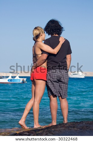 Young romantic couple watching boats on the beach