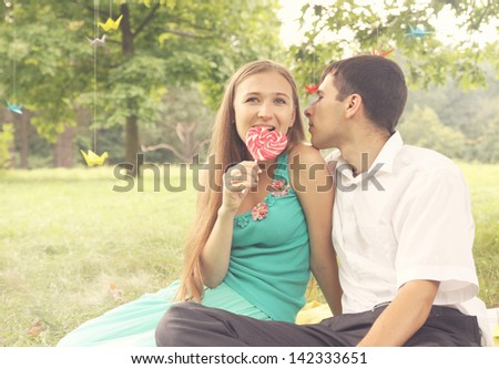 young romantic couple  with candy on nature - stock photo