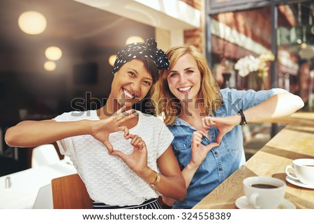 Young romantic female friends sitting in a restaurant together enjoying coffee making heart shaoed signs with their hands as they laugh at the camera, multiethnic couple - stock photo