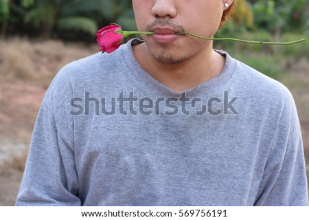 Young romantic man is holding a red rose in his mouth on nature blurred background. Love and romance Valentine's day concept.