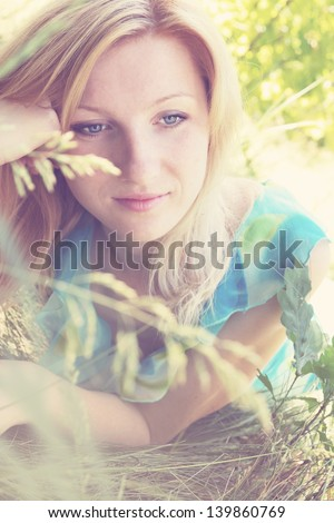 Young romantic pensive woman dreaming in nature - stock photo