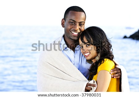 Young romantic sharing a blanket by the ocean - stock photo