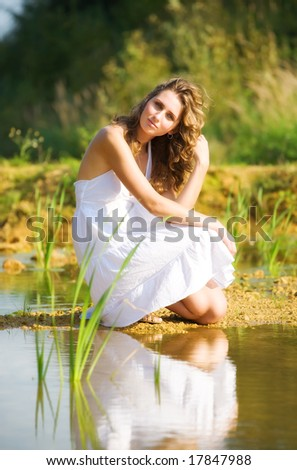 Young romantic woman on a river bank. - stock photo