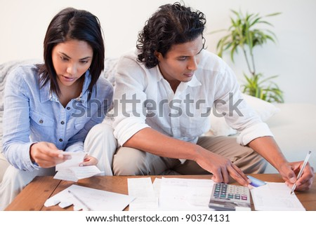 Young room checking bills in the living room - stock photo